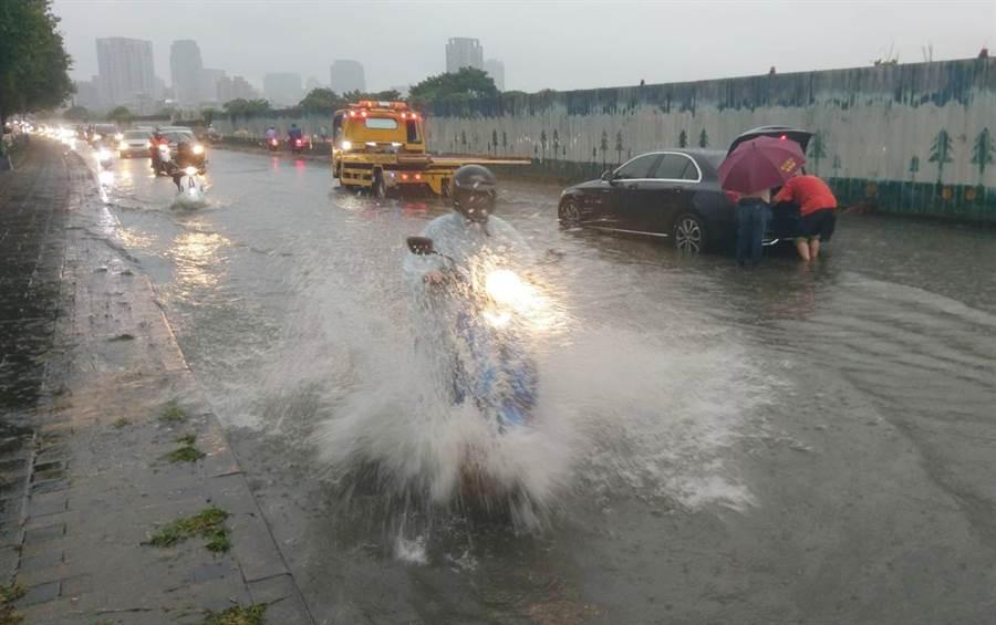 台中市13日下午下起豪大雨,麻園頭溪水暴漲,造成永春東二路及永春東三路淹水,不少機車強行通過,也有車輛拋錨,拖吊車救援中。(黃國峰攝)