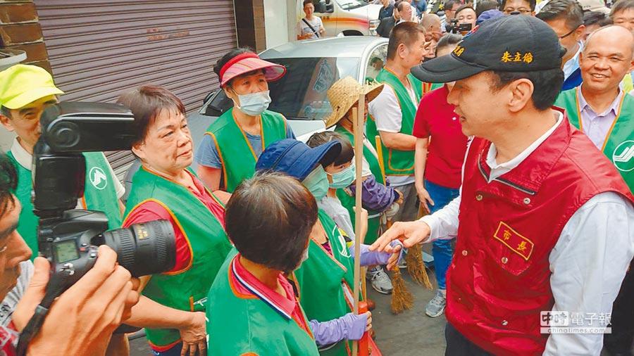 新北市長朱立倫(右)12日視察新莊建安里防疫工作,逐一向在路上打掃清潔人員問候並表達感謝之意。(吳岳修攝)