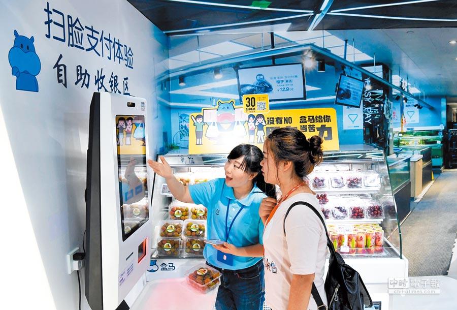 大陸的新零售浪潮正席捲各行各業,圖為民眾在「盒馬鮮生」展區前體驗「刷臉結算」服務。(中新社)