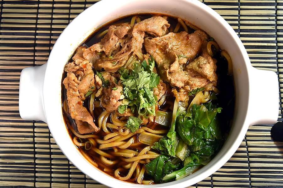 〈伊宛大肉麵〉的湯頭是以豬大骨湯加了滷豬腳的滷汁,以及大量蒜蓉熬製,並加了香菜添香。(攝影/姚舜)