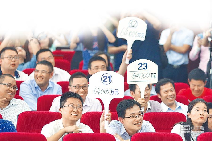 南京兩筆土地拍賣雖競爭激烈,但最終成交價卻比之前的地王低。圖為房企代表舉牌競標。(中新社資料照片)