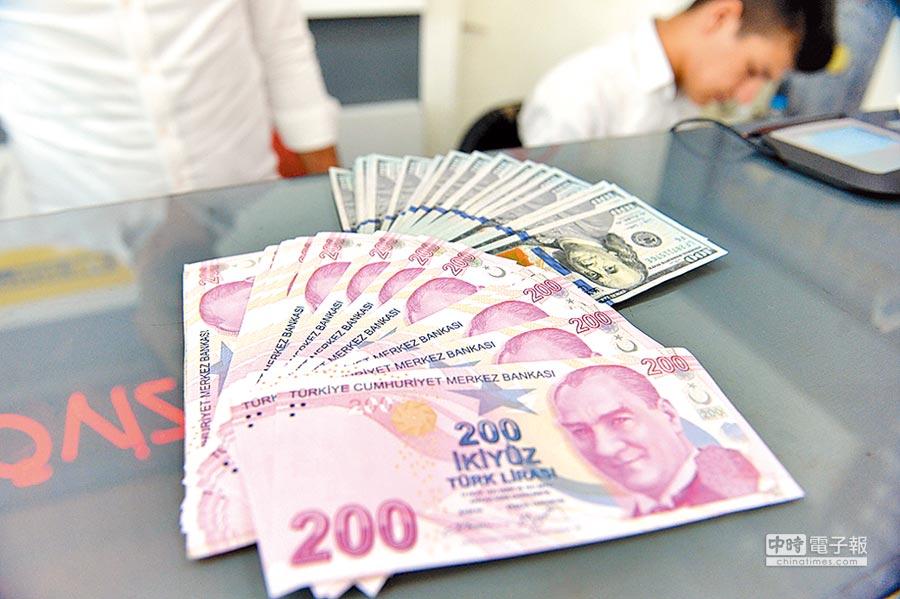 美國發動對土耳其關稅戰,里拉崩盤。圖為土耳其安卡拉的一名男子展示土耳其里拉和美元紙幣。(新華社資料照片)