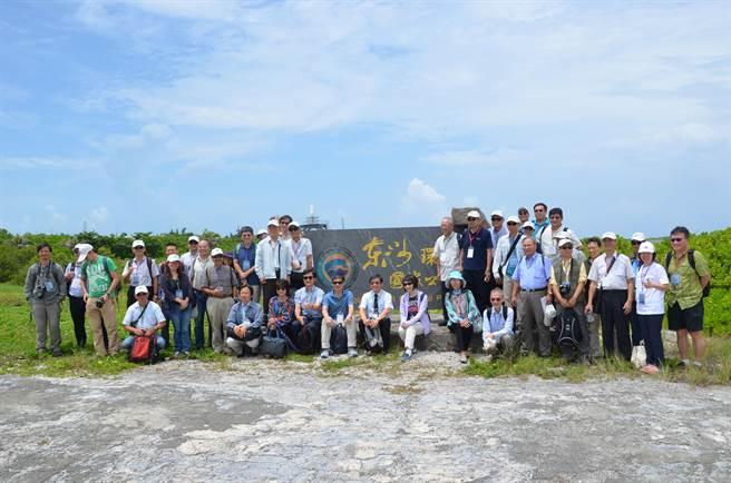 科技部部長陳良基今(17)日率團登上東沙島,進行科學研究工作會議及現勘,團員於東沙國家公園碑合影。(科技部提供)