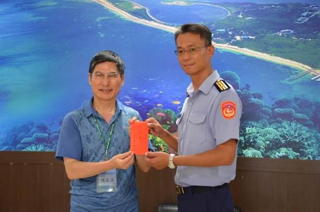 科技部部長陳良基(左)致贈加菜金給海巡署東沙指揮部指揮官熊同中。(科技部提供)