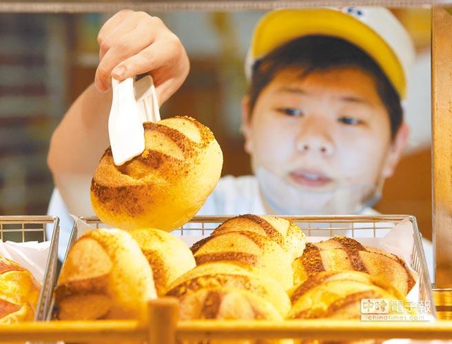 基本工資將調漲5%,全國工業總會代表何語不諱言,店家勢必將成本轉嫁到消費者身上。圖為麵包店員工忙著將麵包上架。(本報資料照片)