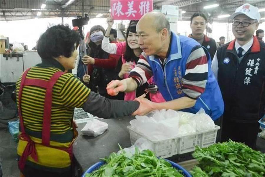 韓國瑜與菜販熱情握手,還不忘告訴對方:「我以前也是賣這些菜,一樣的!」(本報系資料照片)