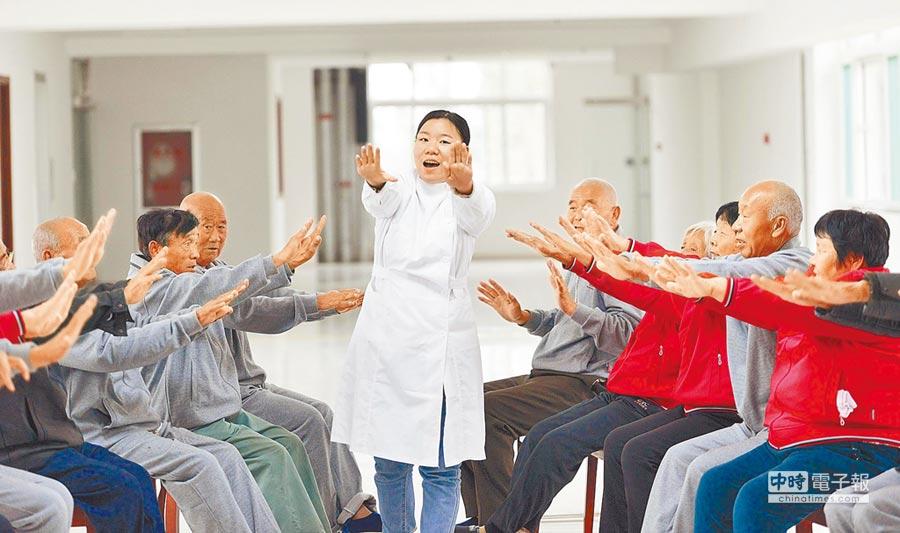 山東鄒平縣魏橋鎮養老服務中心人員指導老人鍛鍊肢體。(新華社資料照片)