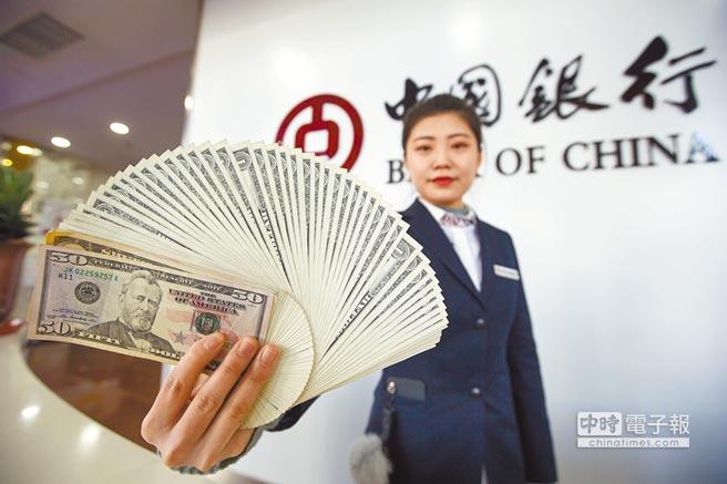 大陸外幣存貸款連續3個月雙降,圖為銀行工作人員展示美元。(中新社資料照片)
