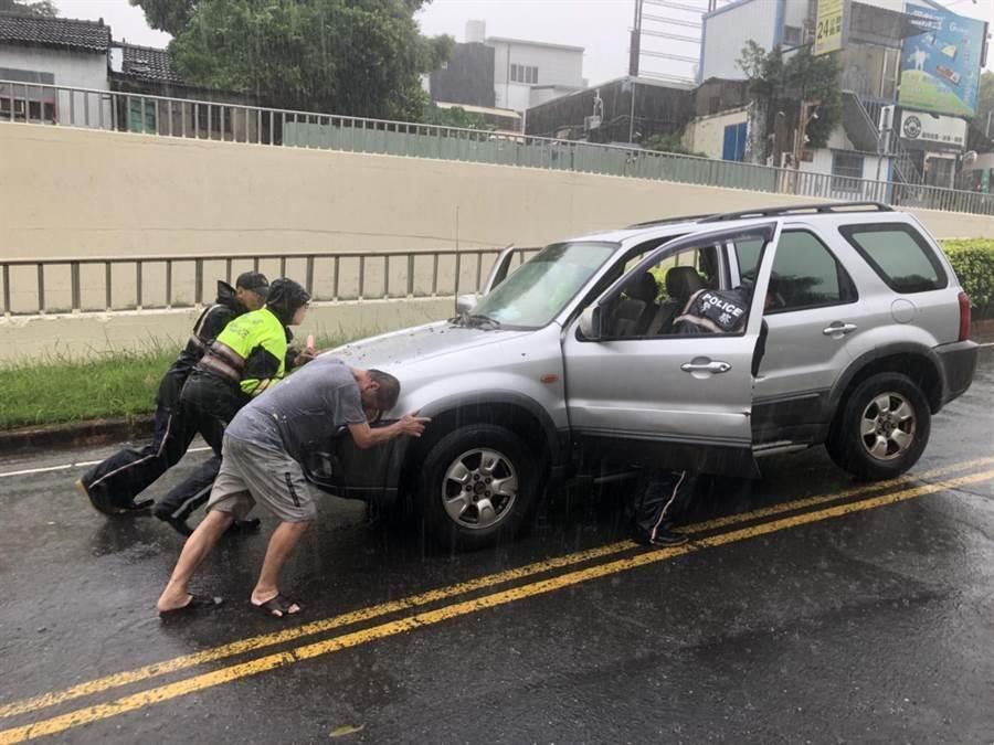 警方一起將郭姓駕駛泡在水裡的汽車推向高處。(程炳璋翻攝)