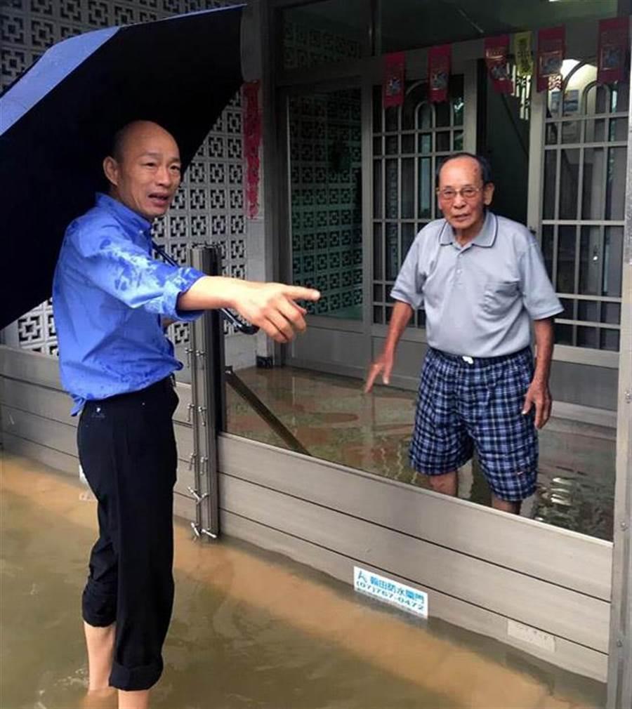 韓國瑜(左)捲起褲管,赤腳走進淹水的高雄旗山區。(李義翻攝)