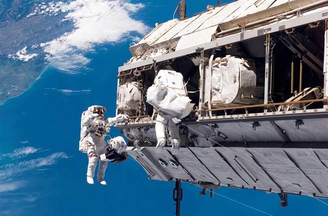 圖為國際太空站上的太空人進行太空漫步,組裝太空站部件。(圖/美聯社)