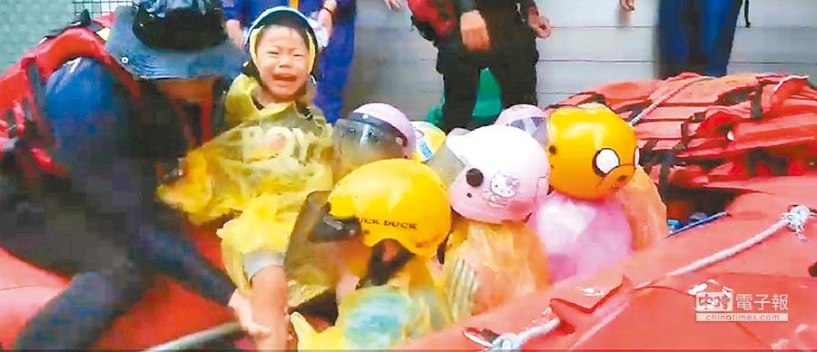 台南市仁德區中華醫事科大校園淹水嚴重,華醫附設幼兒園孩童受困,消防局出動橡皮艇馳援,幼童嚇得哇哇大哭。(曹婷婷攝)