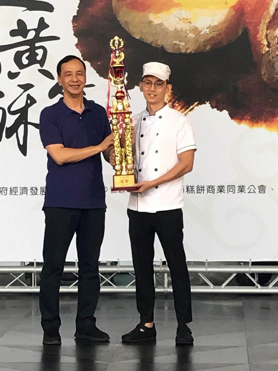 新北市長朱立倫頒發獎杯給蛋黃酥節得獎店家。(陳俊雄攝)