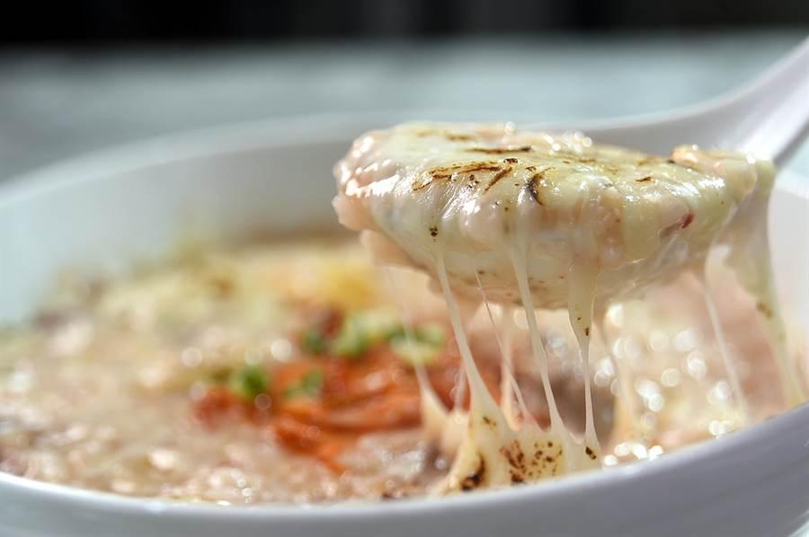 〈HUHA〉的〈起司泡妞粥〉因舖灑了起司條再在表層炙燒,用湯匙舀粥時會「牽絲」。(圖/姚舜)