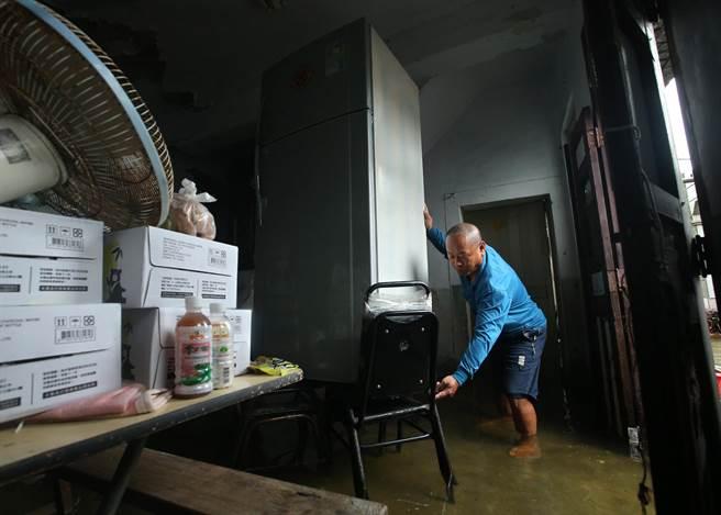 高雄29日持續大雨導致林園中汕里北汕路一帶巷內民宅依然淹水,王姓住戶將冰箱墊高以免泡湯,他說28日前1天還淹到椅子高度。(王錦河攝)
