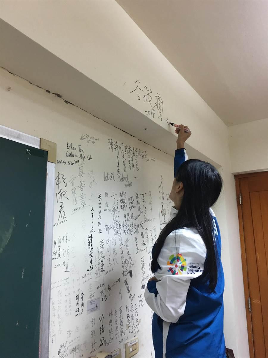 谷筱霜在母校榮譽牆最高處簽名。(沈揮勝攝)