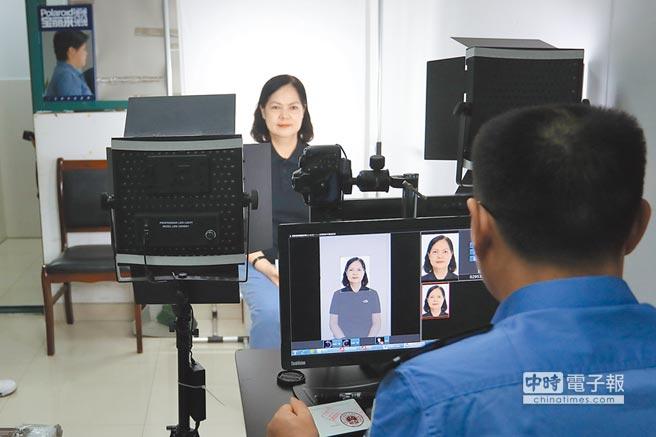 申領過程中,大陸民警為台灣同胞拍攝標準照。(中新社)