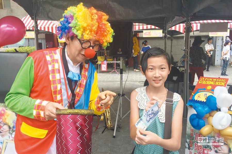 街頭藝人廖錦忠表演把百元變成千元鈔的魔術,讓小朋友驚奇不已。(陳慶居攝)
