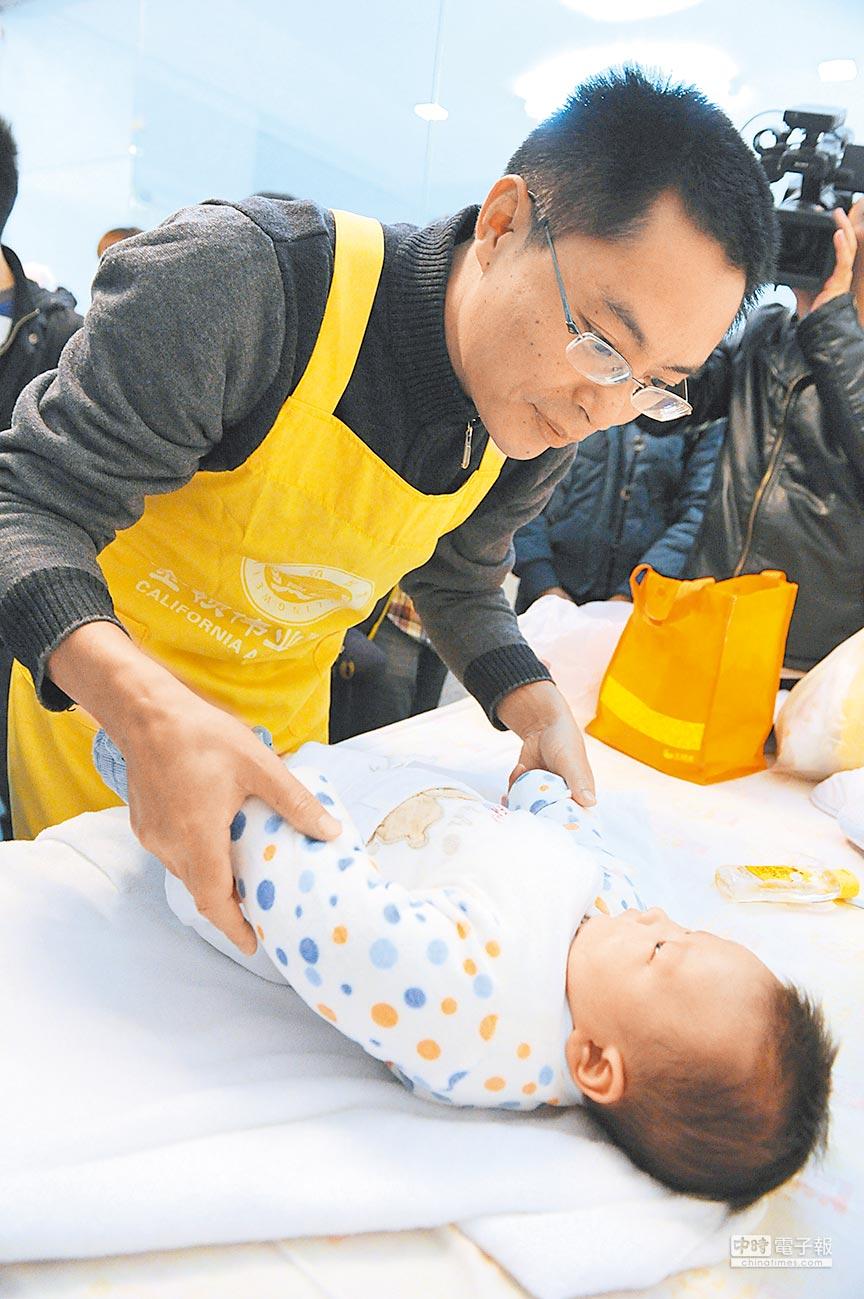 大陸一名大學老師轉行學做「男月嫂」,在長沙某醫院對嬰兒進行撫觸學習。(中新社資料照片)