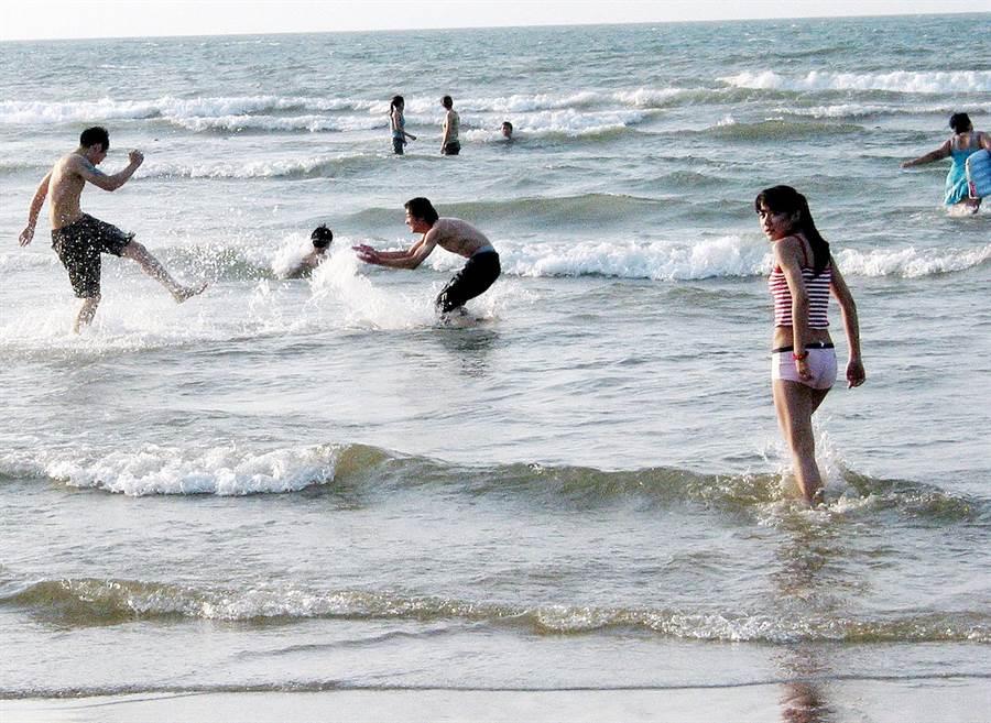 圖為假日時的石門白沙灣海域,民眾戲水情形。(本報系資料照/柯承惠攝)