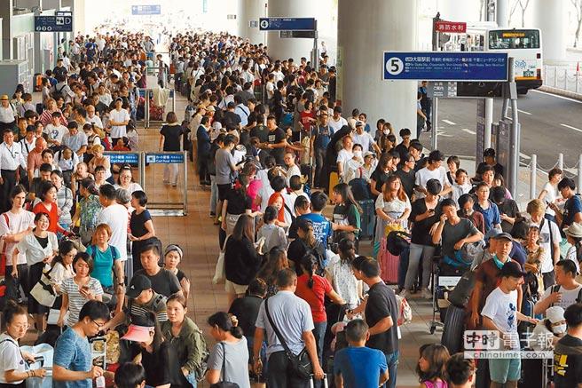 燕子強颱狂掃日本,被迫滯留在關西國際機場的大量旅客5日搭乘巴士等交通工具撤離。(法新社)