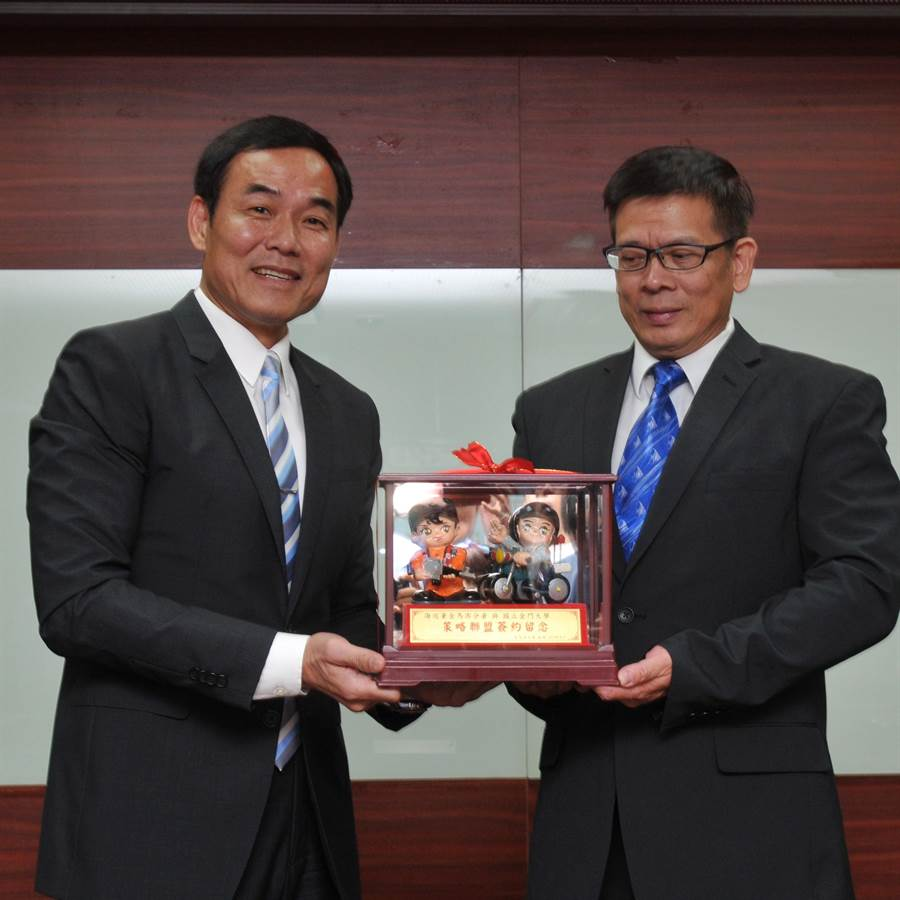 廖德成分署長(左)致贈金大「海巡公仔」,由校長陳建民代表接受。(李金生攝)