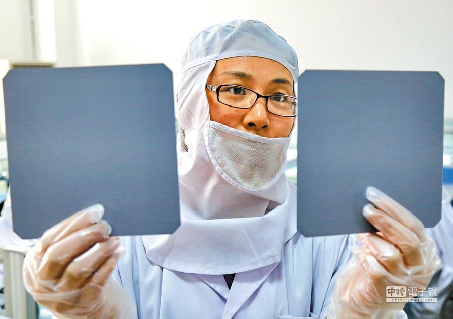 大陸半導體成全球最大市場,但晶片自給率僅14%。圖為河北工人檢查單晶矽片品質。(新華社資料照片)