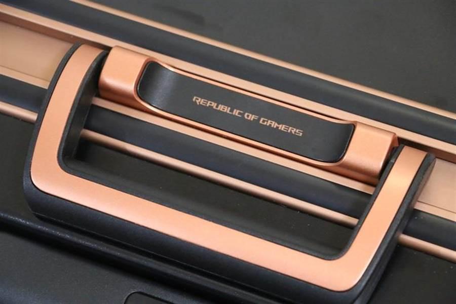 華碩ROG Phone全配加贈的行李箱以黑+銅的配色,相當亮眼。頂端握把還印有ROG品牌字樣。(圖/黃慧雯攝)