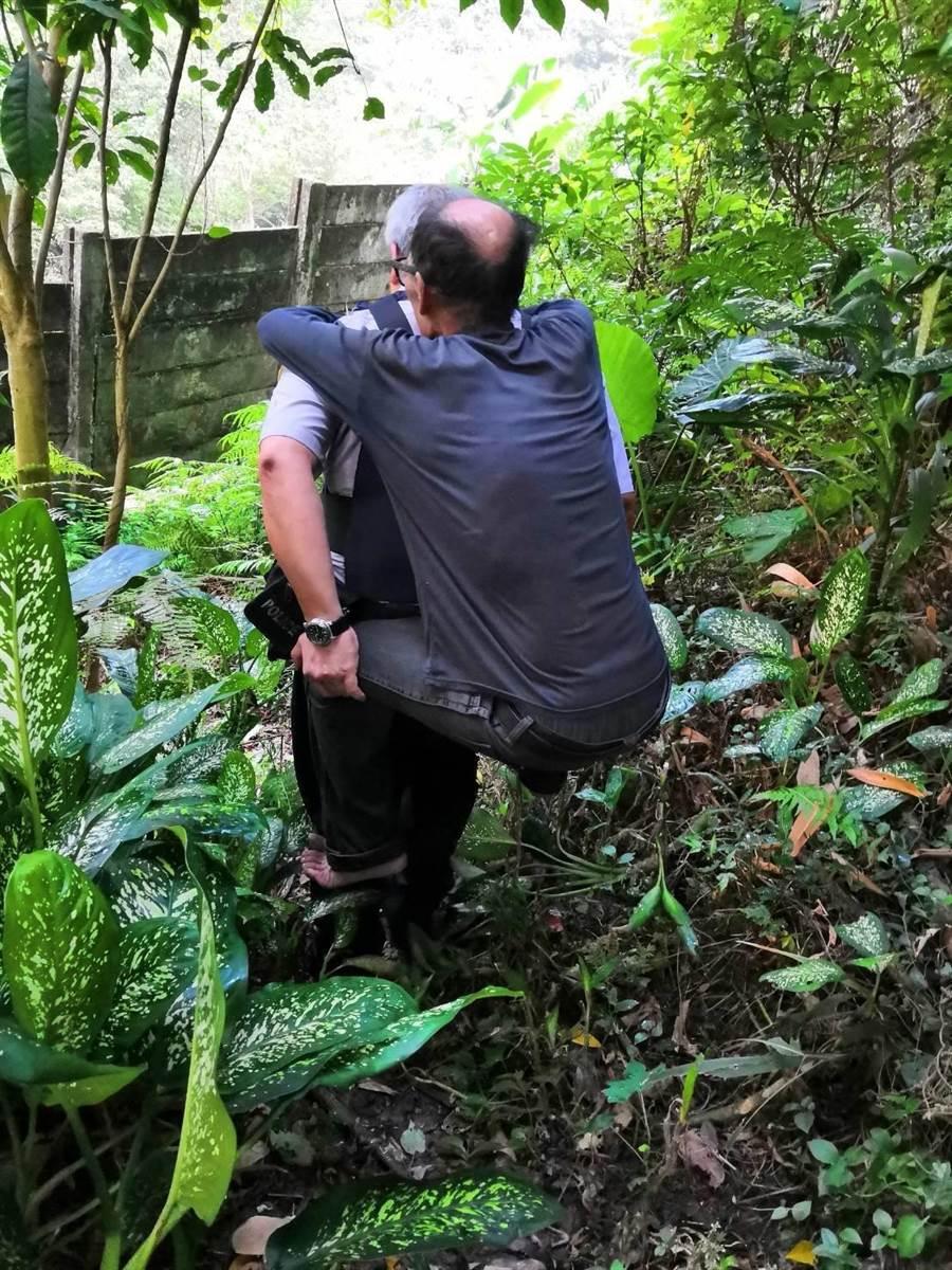 文山一分局指南所員警劉高宏日前協助背負林姓老翁安全下山。〔警方提供〕