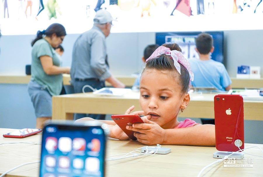 蘋果將iPhone組裝移回美國,恐令手機售價提升。圖為一名女孩在紐約一家蘋果專賣店試用商品。(新華社資料照片)