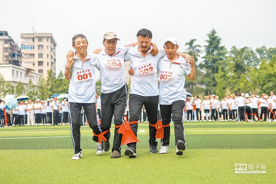 5月17日,湖南老年大學舉辦趣味體育運動會,老人們進行「四人五足」接力比賽。(新華社)
