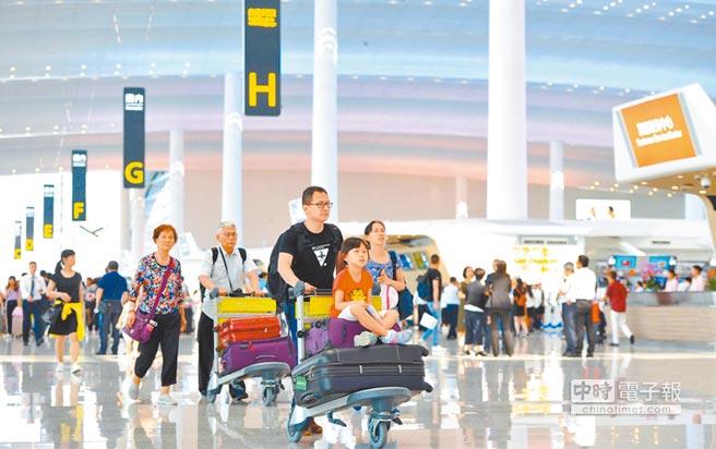 大陸民眾在廣州白雲機場準備辦理登機手續。(新華社資料照片)