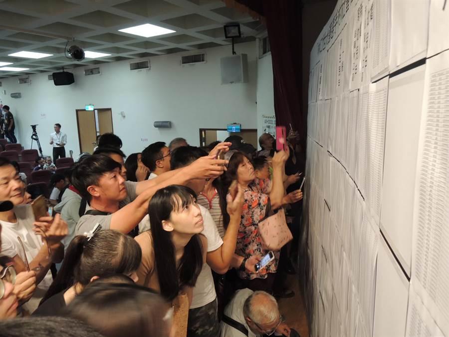 林口世大運選手村社會住宅13日下午舉辦公開抽籤,民眾爭搶查看自己是否中籤。(吳岳修攝)