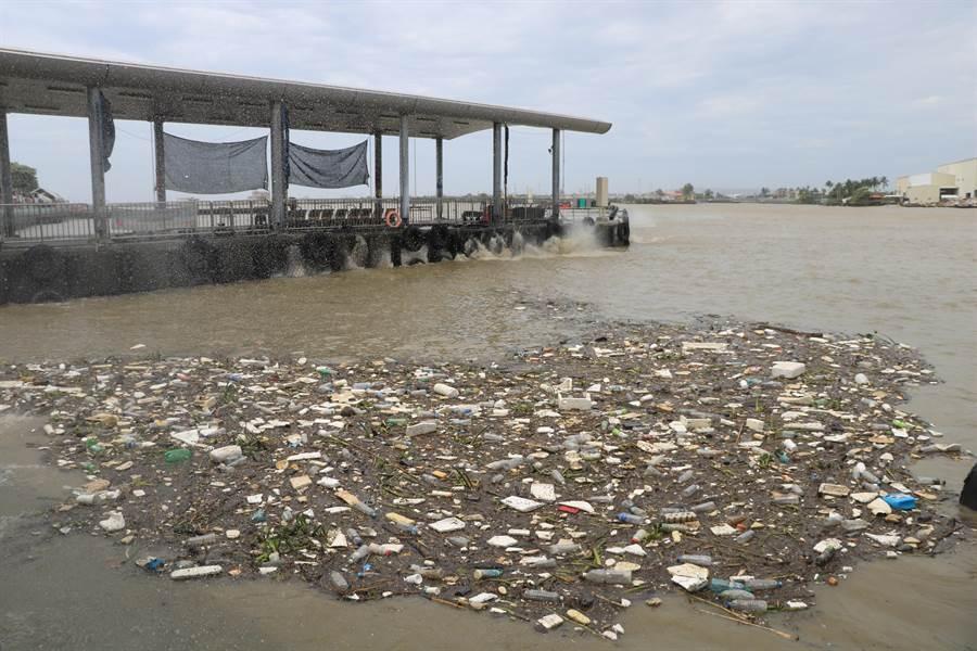 黃濁的大浪一波波打進東港碼頭,聚集一片垃圾浮在水面上。(謝佳潾攝)