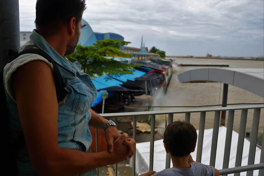 1名來台旅遊的義大利男子,帶著小朋友跑到碼頭2樓觀浪。(謝佳潾攝)