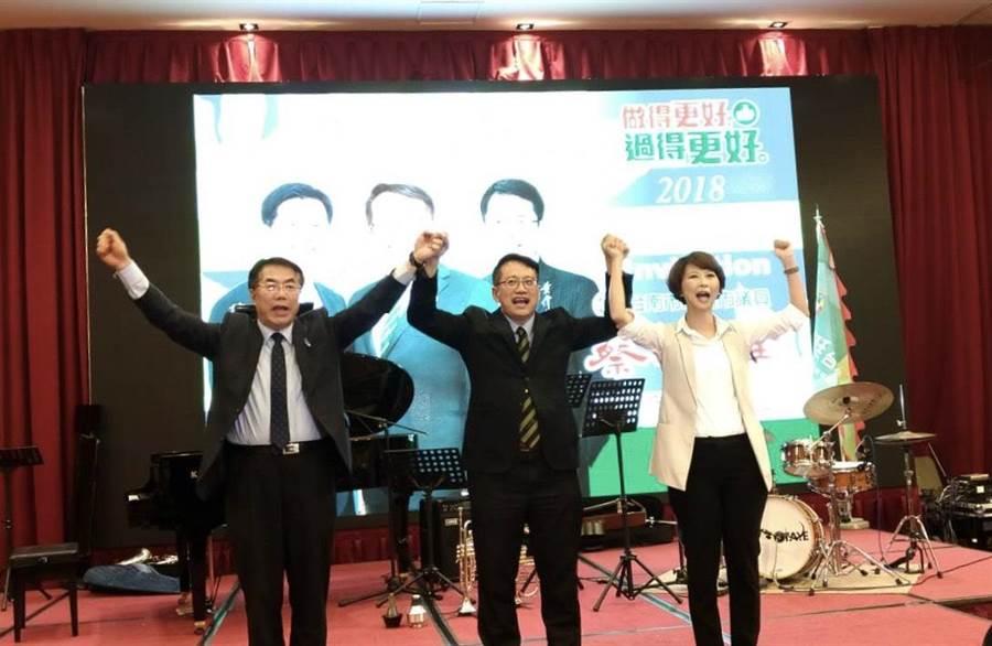 在民進黨台南市長初選時互相攻訐的黃偉哲(左)與陳亭妃(右)高舉蔡旺詮的手喊凍蒜。(蔡旺詮競選總部提供)
