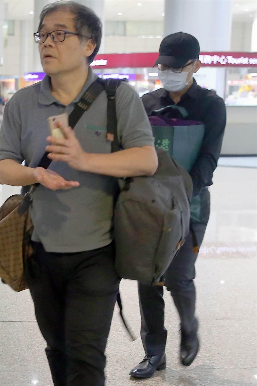 蘇啟誠的親友、兒子17日晚間搭乘華航CI173班機自大阪返台,蘇啟誠的兒子帶著帽子、口罩、著深色衣物,低調抱著骨灰罈前往車道搭車,全程不發一語,在與外頭等候的家屬會合後,隨即上車離去。(陳麒全攝)