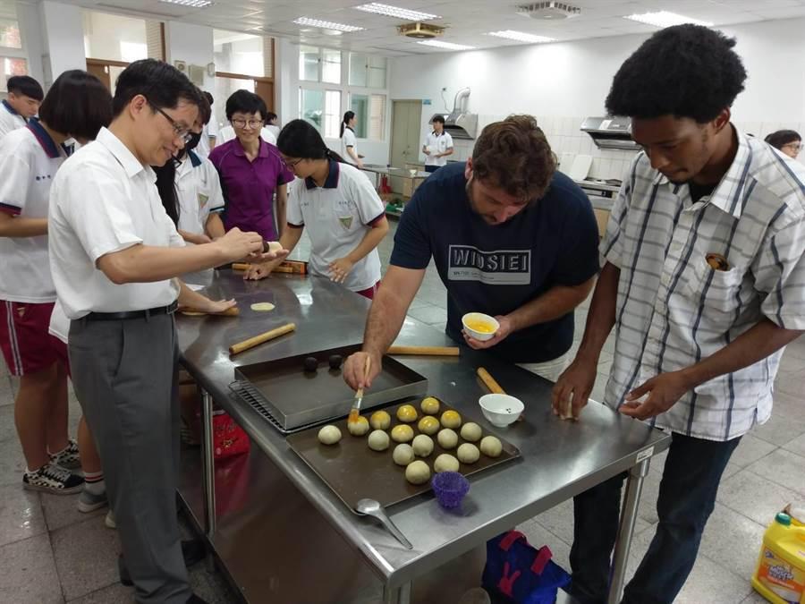 19日上午新化高中校長鄭曜忠(左)邀請聖露西亞外籍生Tsebe Victorin(右一)、西班牙籍台灣女婿Julio Ramos(右二)和學生一起參與學習做蛋黃酥活動。(李其樺攝)