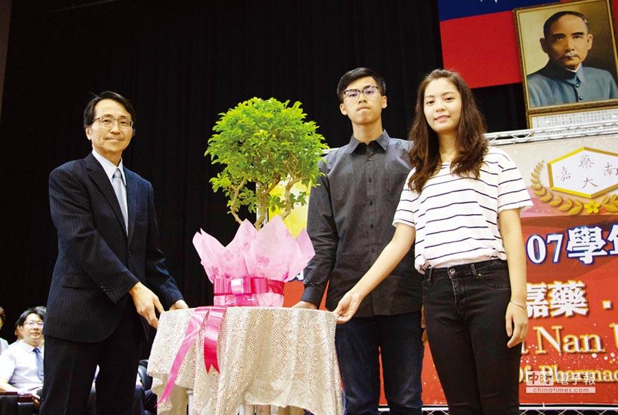 校長陳鴻助(左一)致贈小樹苗予新生代表;圖右一港生范嘉珍、右二許勝瑋。圖/周榮發