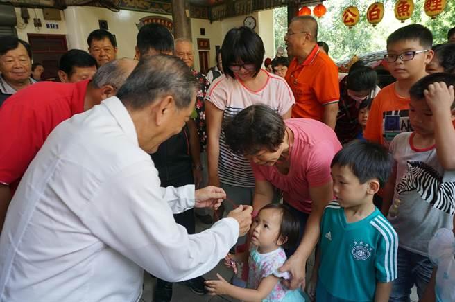 台中市副市長林陵三(左)為小朋友「戴絭」,祈求石母娘娘庇佑孩童平安順利長大。(王文吉攝)
