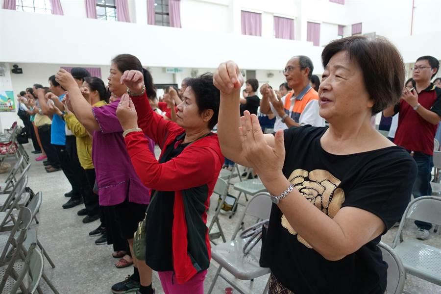 斗六市公所政風室自編「選舉顧未來」手語歌,此一動作是「歪哥」,意為把錢收進袖子。(周麗蘭攝)