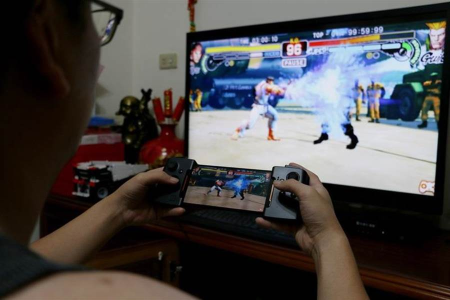 ROG Phone搭配華碩WiGig無線投影基座與GAMEVICE手把(前)。(圖/黃慧雯攝)