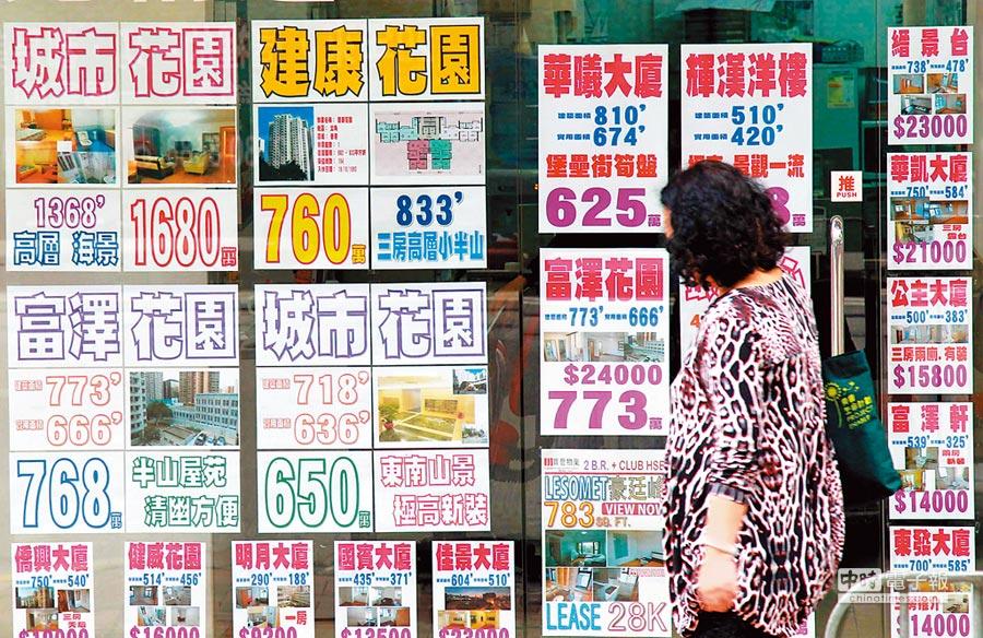 香港樓市面臨轉捩點。圖為市民從地產仲介廣告前經過。(中新社)