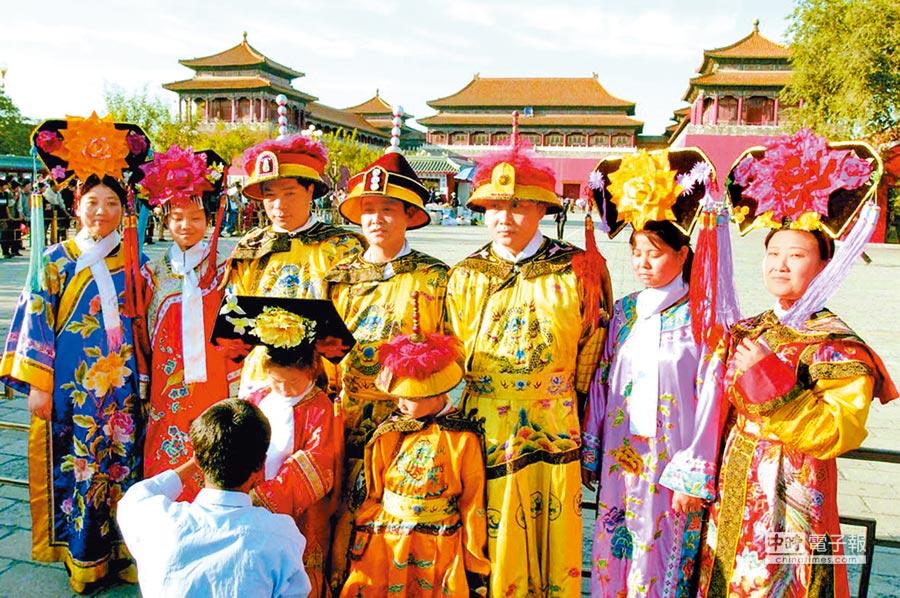 清宮劇帶動文旅融合趨勢。圖為旅客穿古裝在北京故宮前拍照。(中新社)