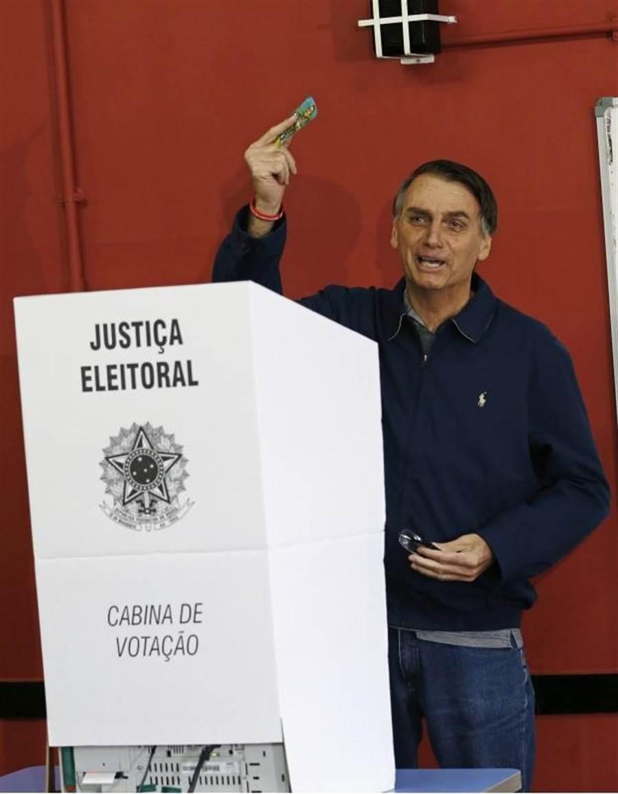 代表社會自由黨角逐巴西總統寶座的波索納洛,7日神情愉快投票。他選前民調領先群雄。(美聯社)