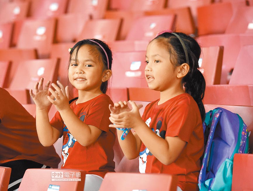 華大研究團隊發現與生雙胞胎機率有關的基因變異。圖為一對可愛雙胞胎小女孩為選手加油。(中新社資料照片)