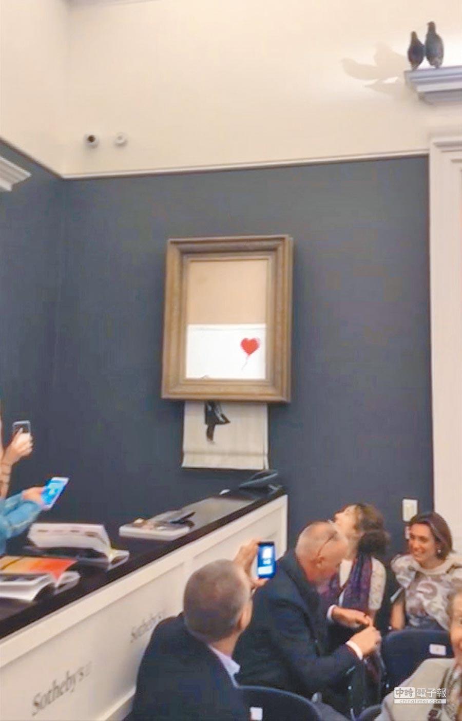 英國著名塗鴉藝術家班克斯作品《氣球女孩》,日前以超過百萬英鎊的價格成交後旋即「自毀」,震驚藝術圈。(美聯社)