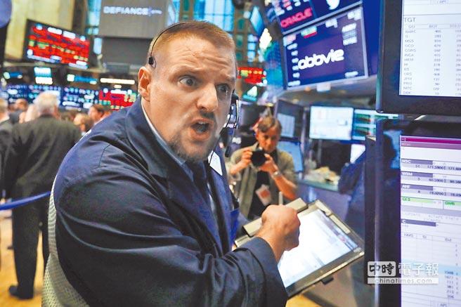 美股三大指數10日全面暴跌,引發全球股災。圖為紐約證券交易所交易員10日忙碌作業,神情緊繃。(美聯社)