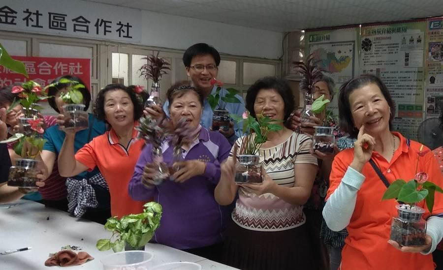 官田區公所區長顏能通與隆田社區發展協會長輩一起展示用菱殼炭製作成的環保植栽。(劉秀芬攝)