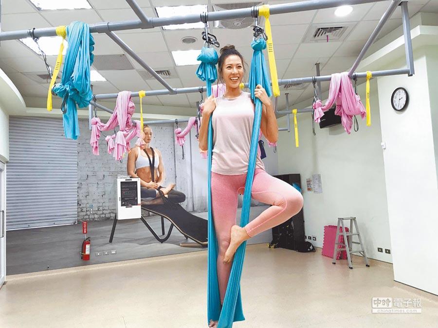 極限運動名模林又立16日在鶯歌運動公園中,示範藉空中瑜珈的掛布來拉筋、鬆開緊繃的肌肉。(陳俊雄翻攝)